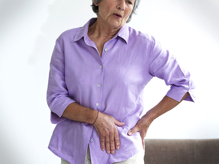 older woman touching her hips in pain