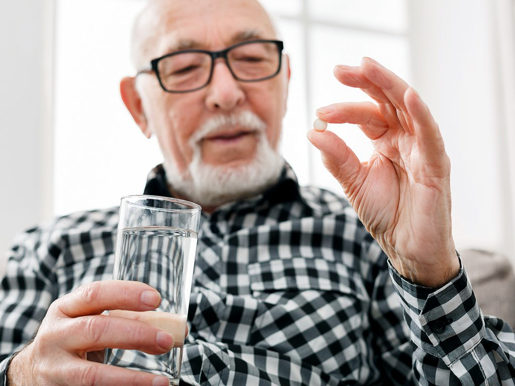 older man with medication and glass of water